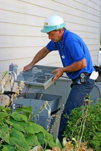 HVAC technician working on AC outdoor unit