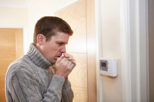 cold man looking at thermostat