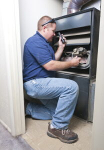 technician-using-flashlight-to-look-at-wiring-in-furnace
