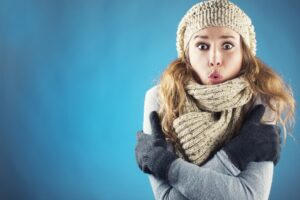 woman-bundled-up-looking-cold-on-blue-background