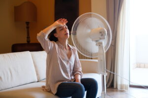 woman-sitting-on-couch-in-front-of-fan