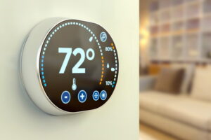 smart-thermostat-on-corner-of-wall-with-couch-in-the-background