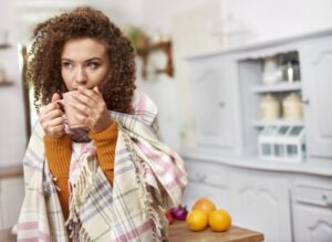 woman-under-blanket-sipping-out-of-mug